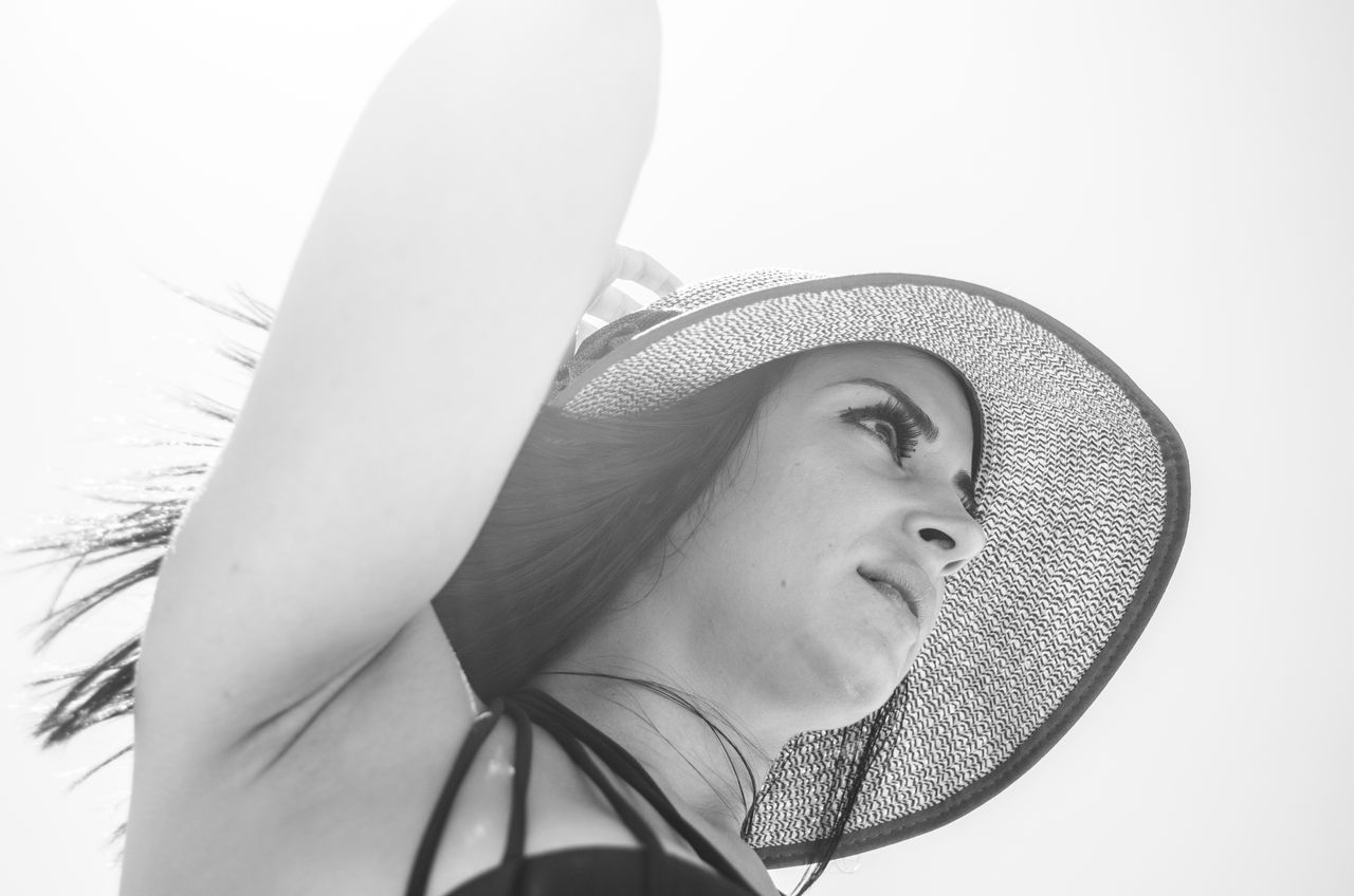 Close-Up Of Young Woman Wearing Hat Against Clear Sky