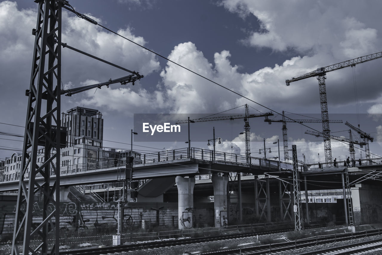 Low Angle View Of Railroad Tracks And Cranes Against Sky