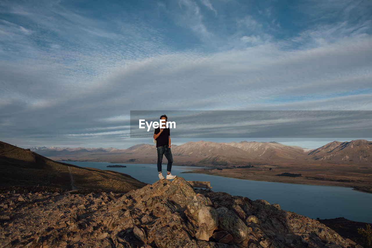 Full length of man standing on cliff against cloudy sky
