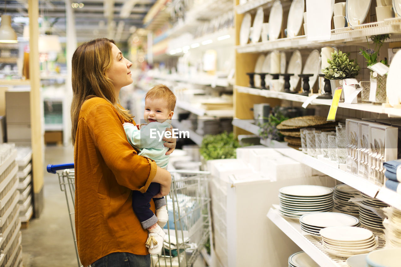 Rear view of mother with daughter standing at store
