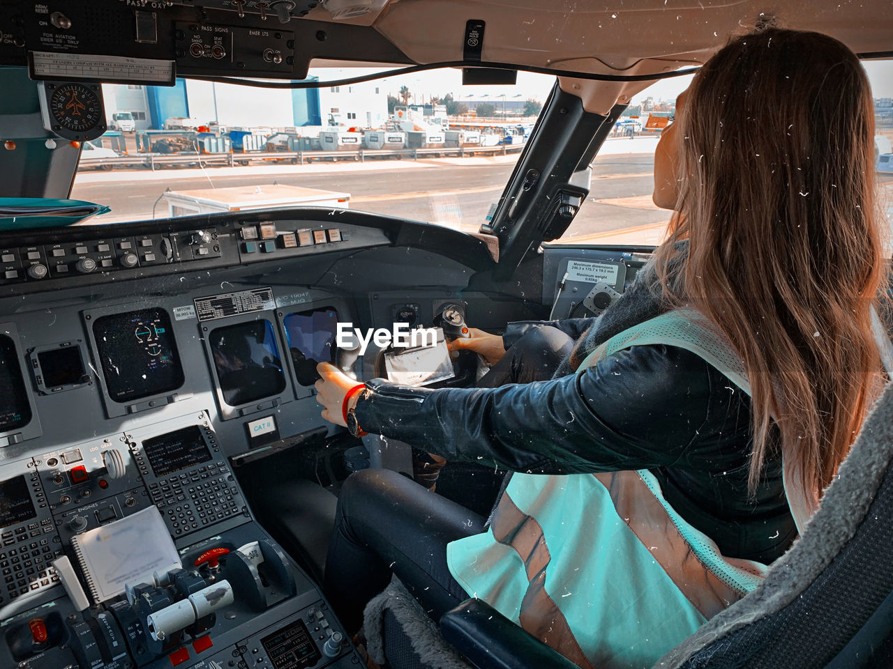REAR VIEW OF WOMAN SITTING IN AIRPLANE AT AIRPORT
