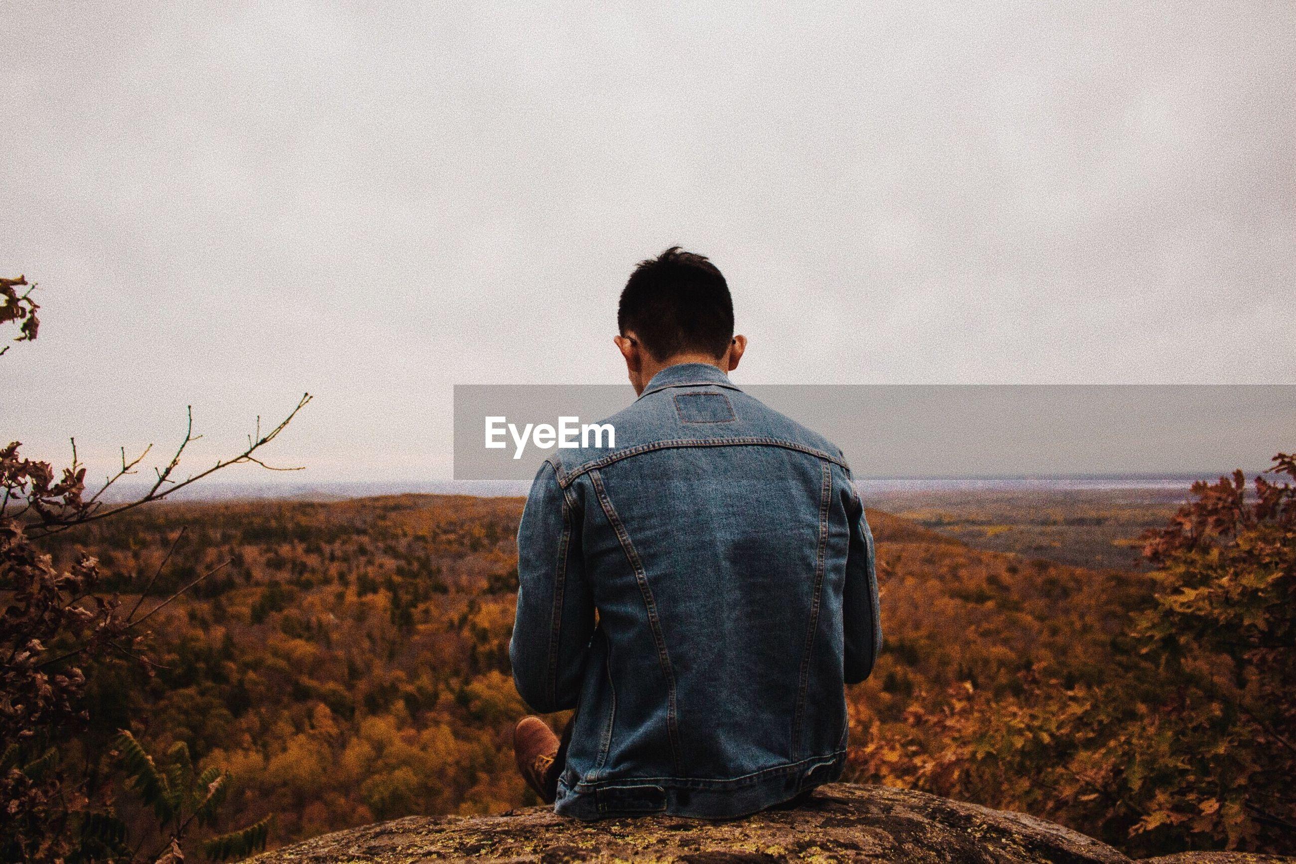 Rear view of man sitting on rocks