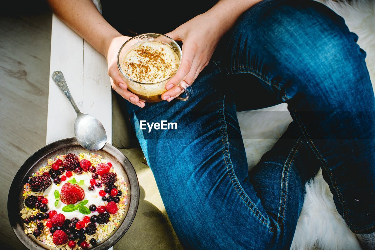 food and drink, one person, food, real people, freshness, casual clothing, lifestyles, human body part, human hand, sitting, hand, fruit, holding, leisure activity, indoors, high angle view, midsection, drink, low section, jeans, glass