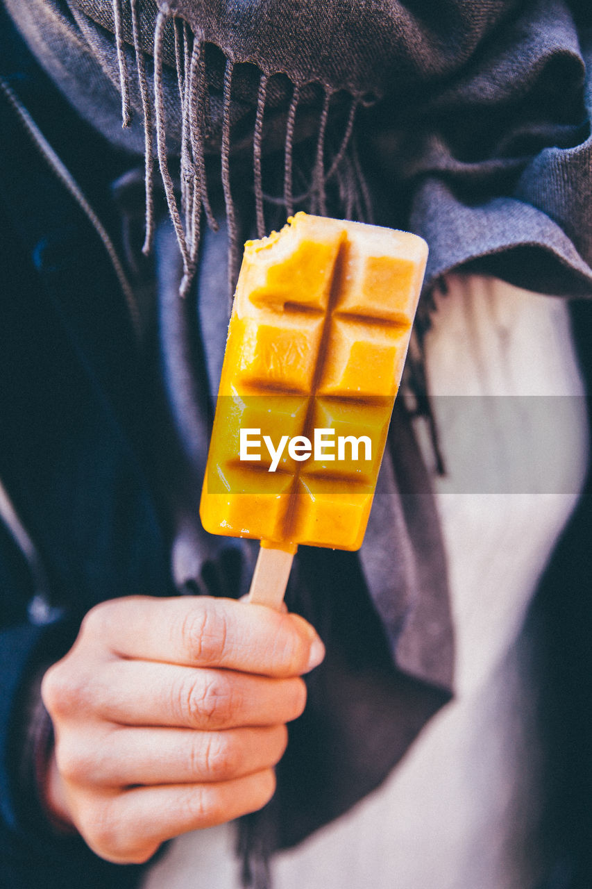 Midsection Of Person Holding Ice Lolly In Autumn
