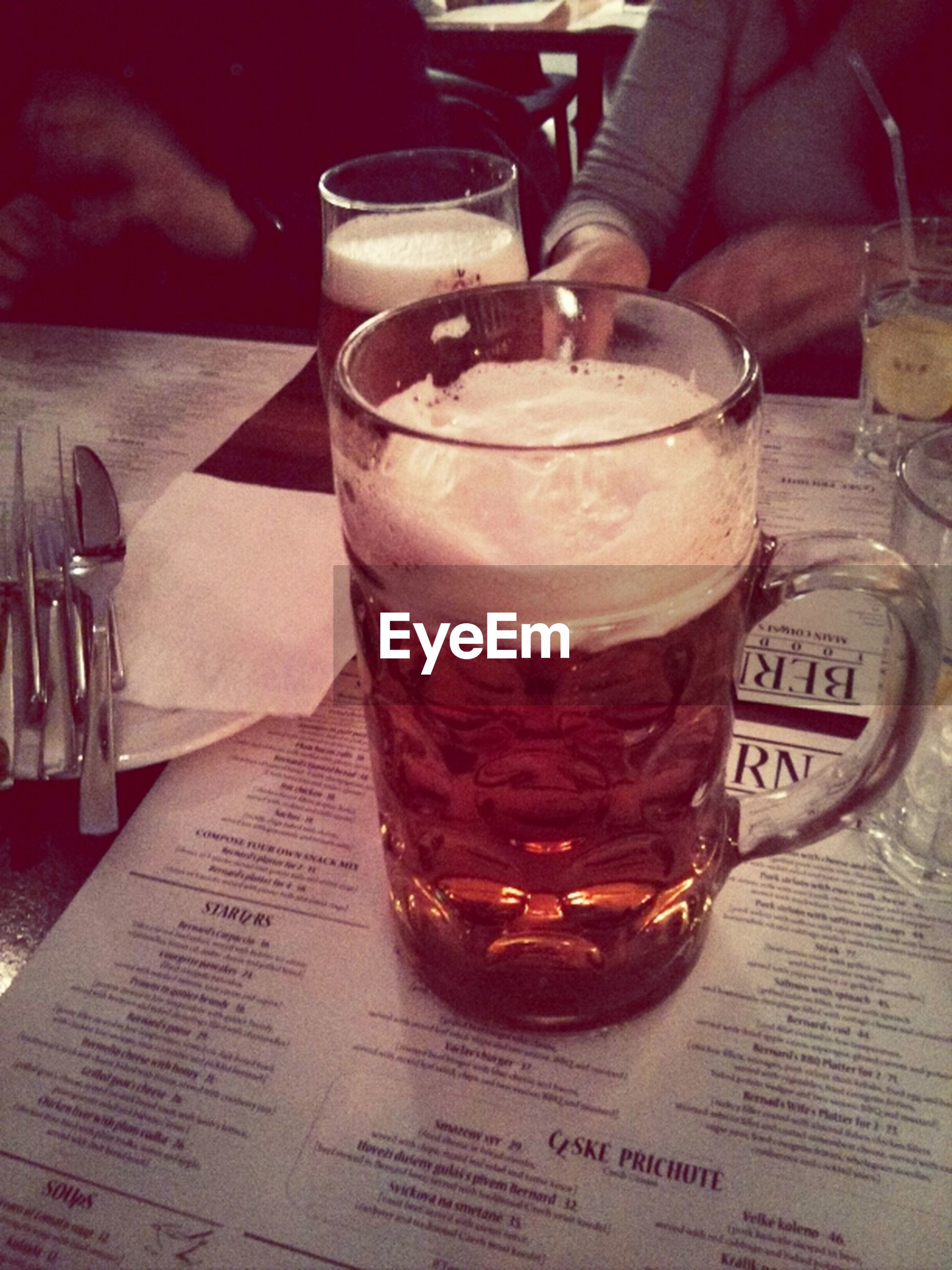 food and drink, drink, indoors, table, freshness, text, refreshment, still life, western script, drinking glass, close-up, alcohol, glass - material, restaurant, communication, no people, focus on foreground, food, wood - material, high angle view