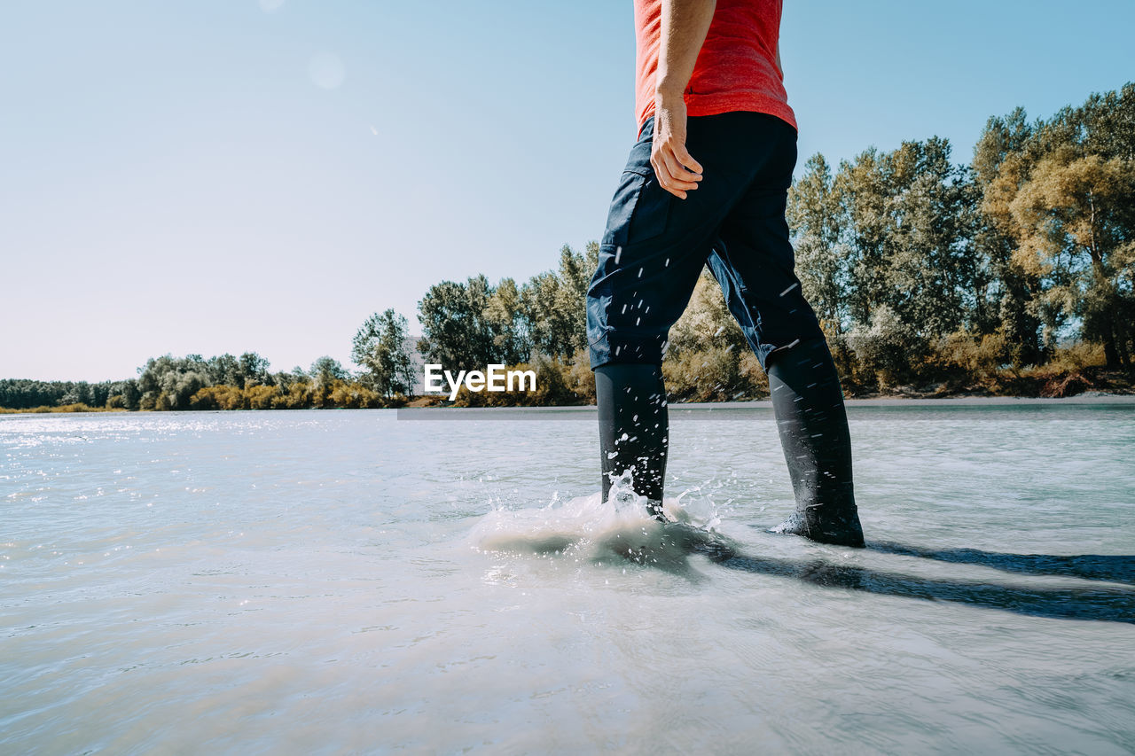 Low section of man in boots standing on riverbank against clear sky