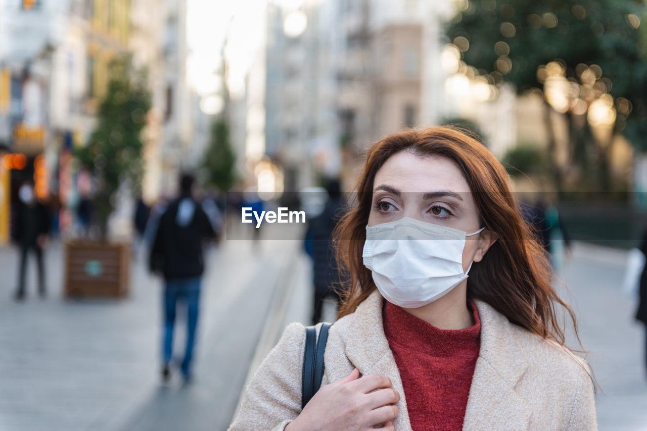 Woman wearing mask looking away standing on city street