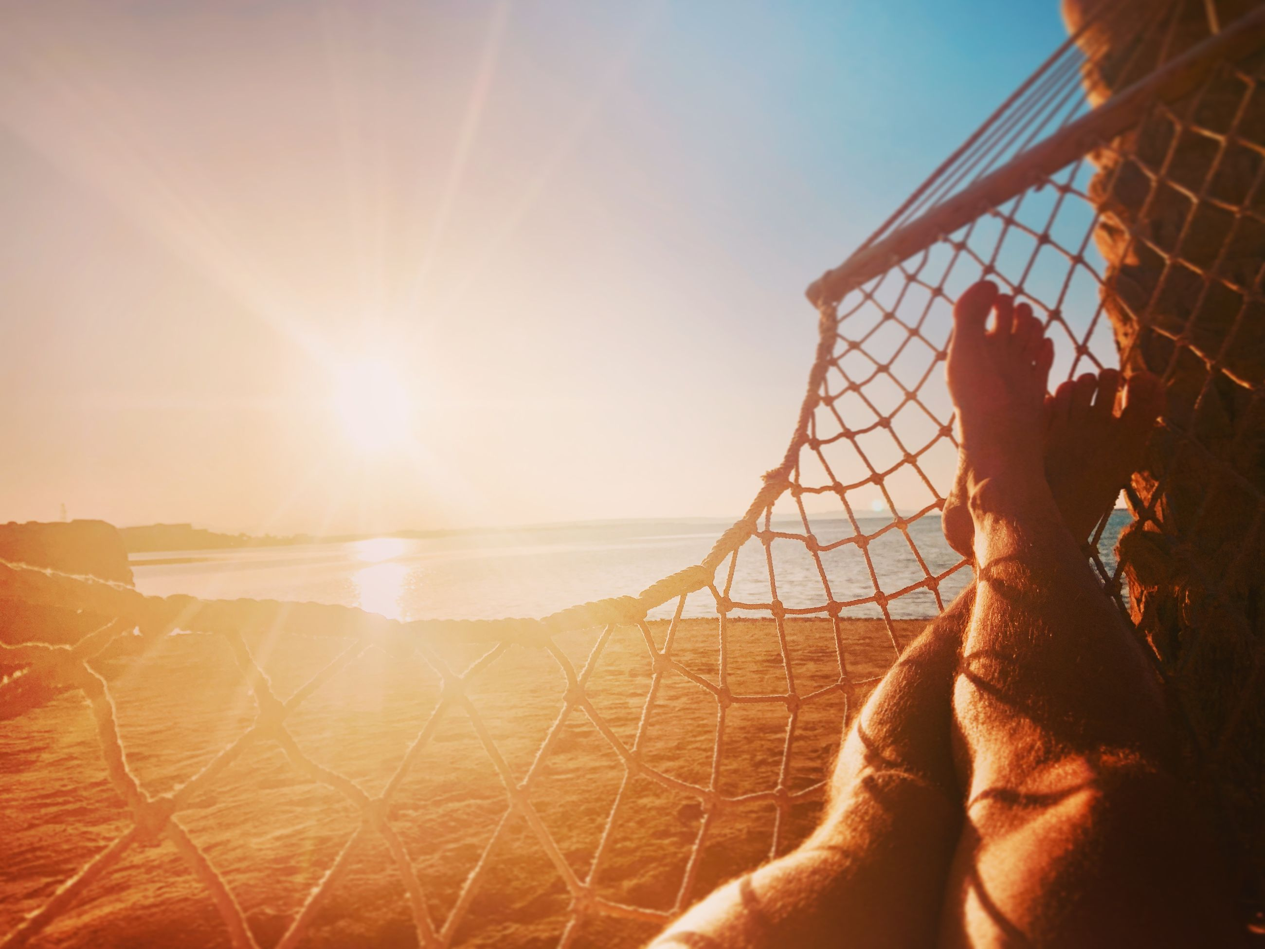 Low section of man relaxing on hammock at beach during sunset