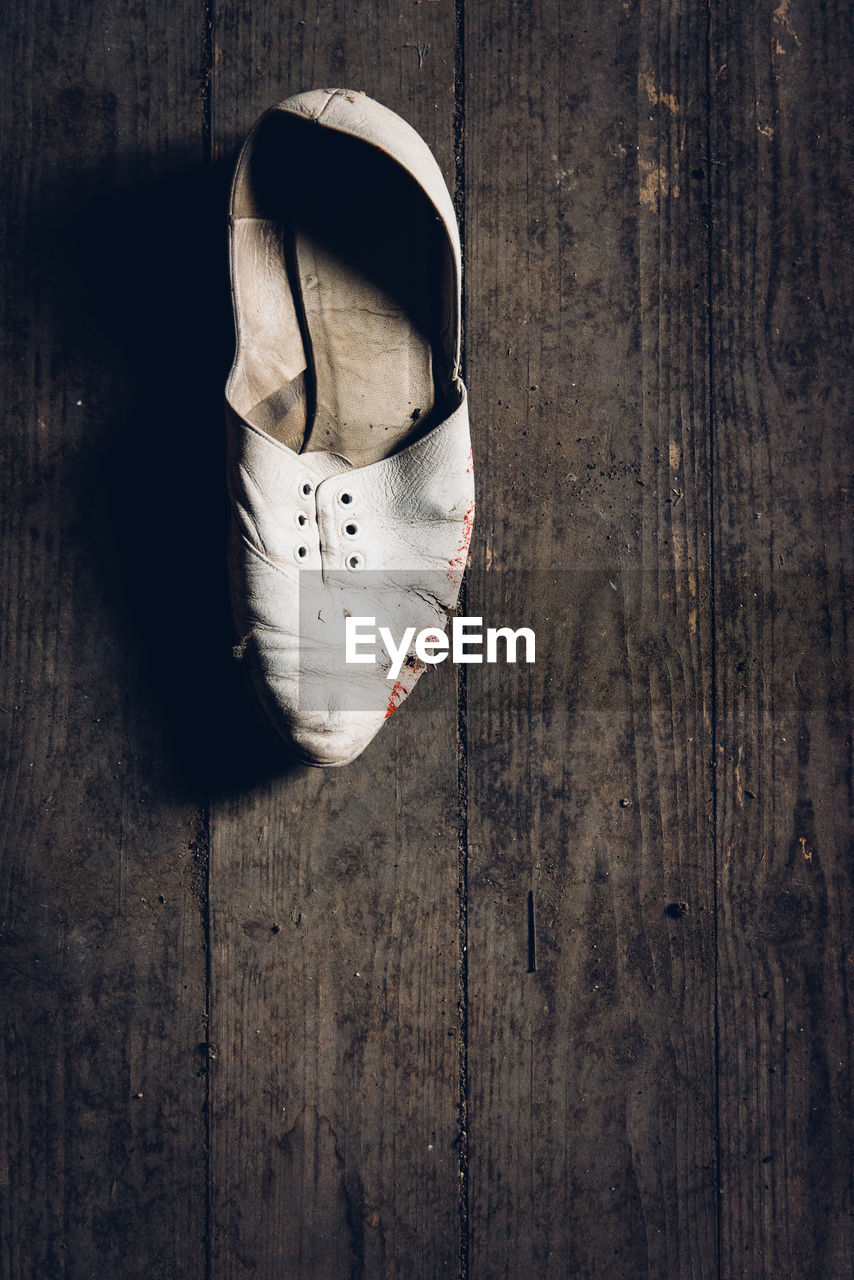 High Angle View Of Abandoned Shoe On Wooden Floor