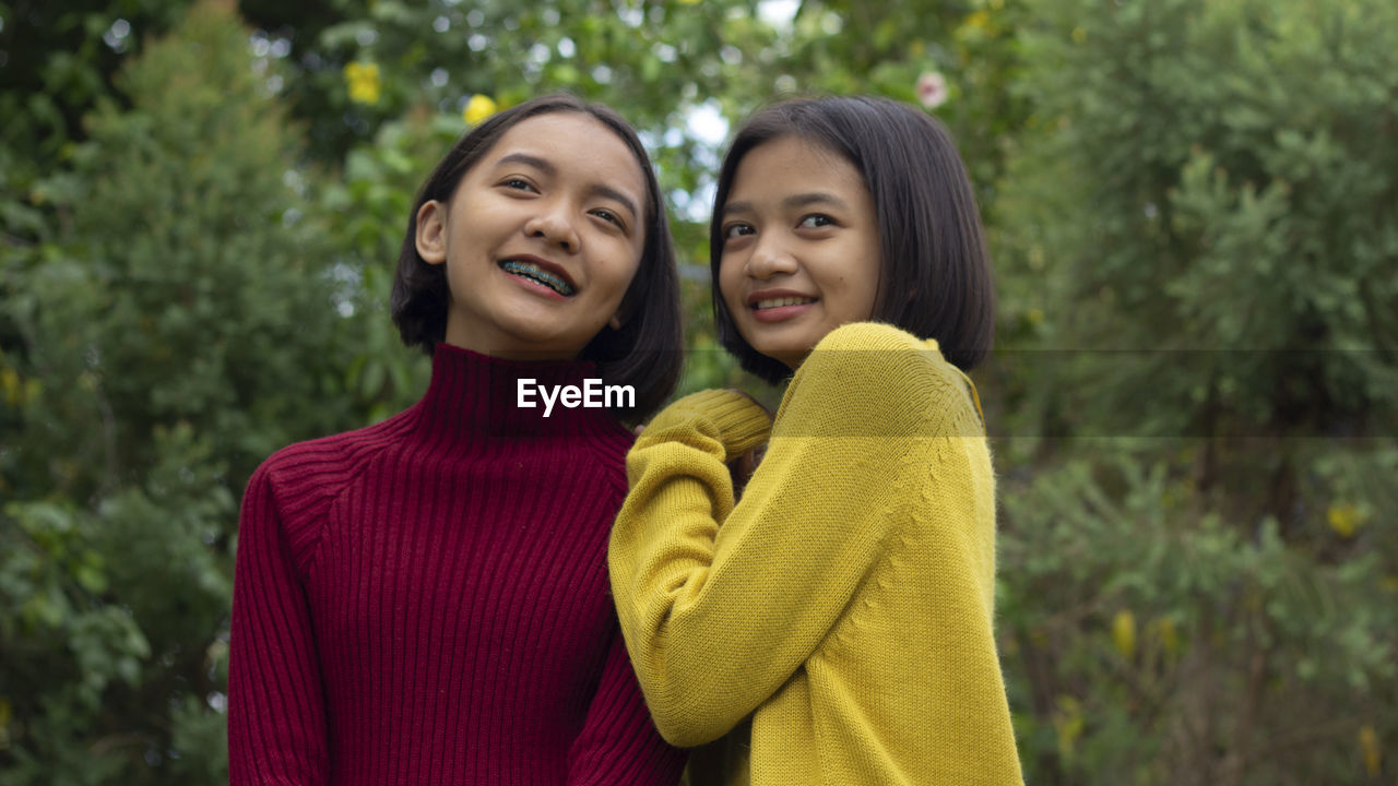 two people, smiling, women, happiness, young women, emotion, young adult, togetherness, portrait, waist up, females, adult, positive emotion, focus on foreground, sweater, casual clothing, clothing, friendship, outdoors, hairstyle