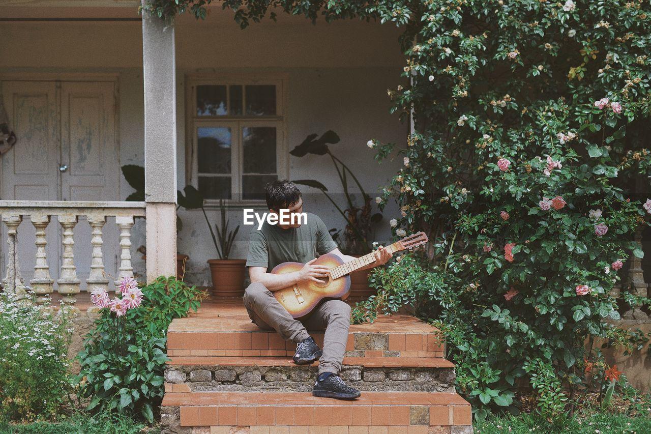 Full Length Of Young Man Playing Guitar At Porch