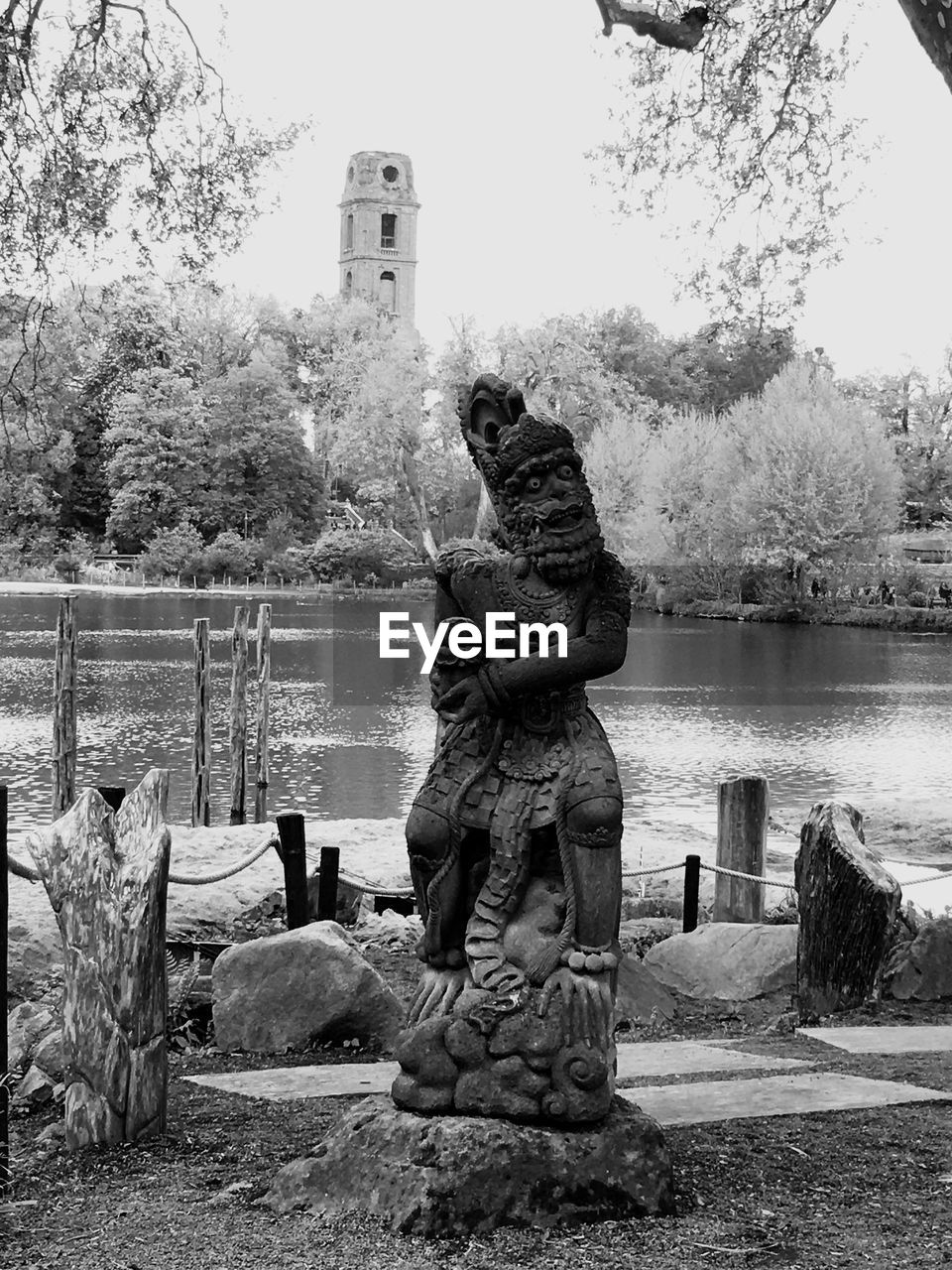 Old sculpture by river during sunny day
