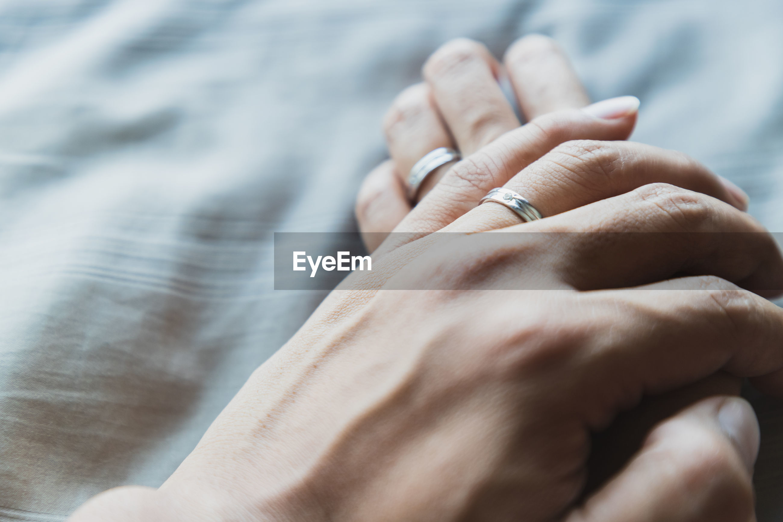 Cropped image of couple holding hands on bed at home