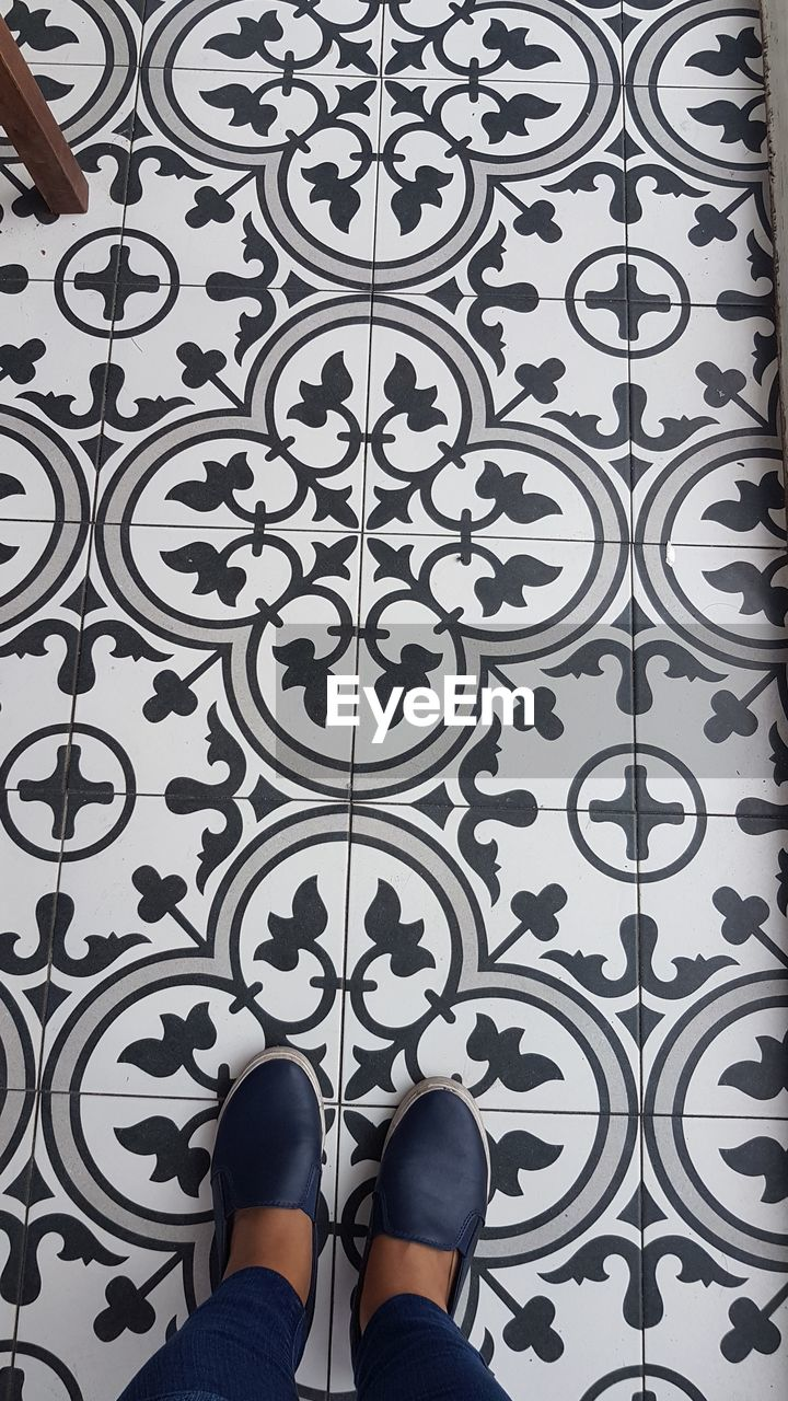 pattern, human leg, low section, one person, personal perspective, standing, shoe, human body part, design, indoors, body part, floral pattern, tile, real people, lifestyles, flooring, women, tiled floor, wallpaper, adult, human foot, human limb