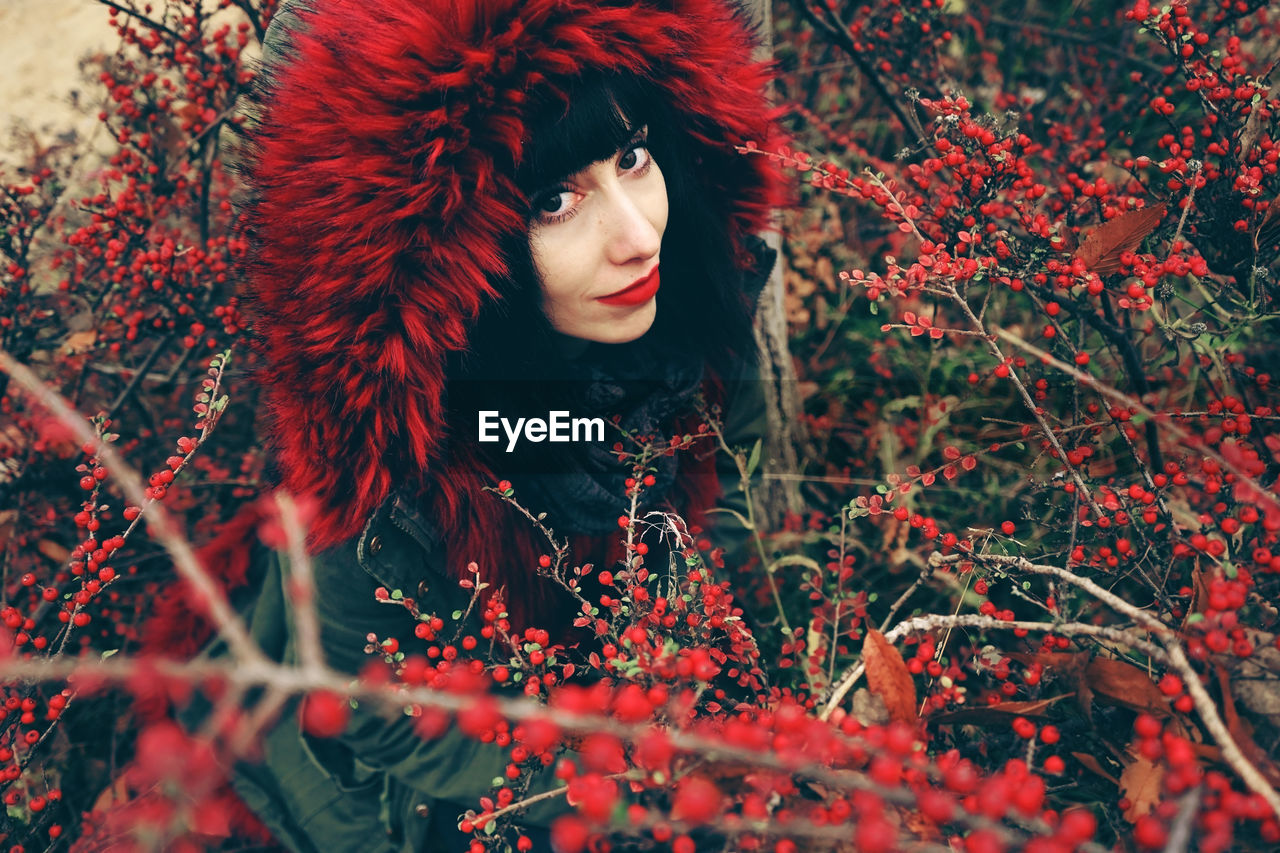 High Angle Portrait Of Woman Wearing Warm Clothing Amidst Red Berries On Plants