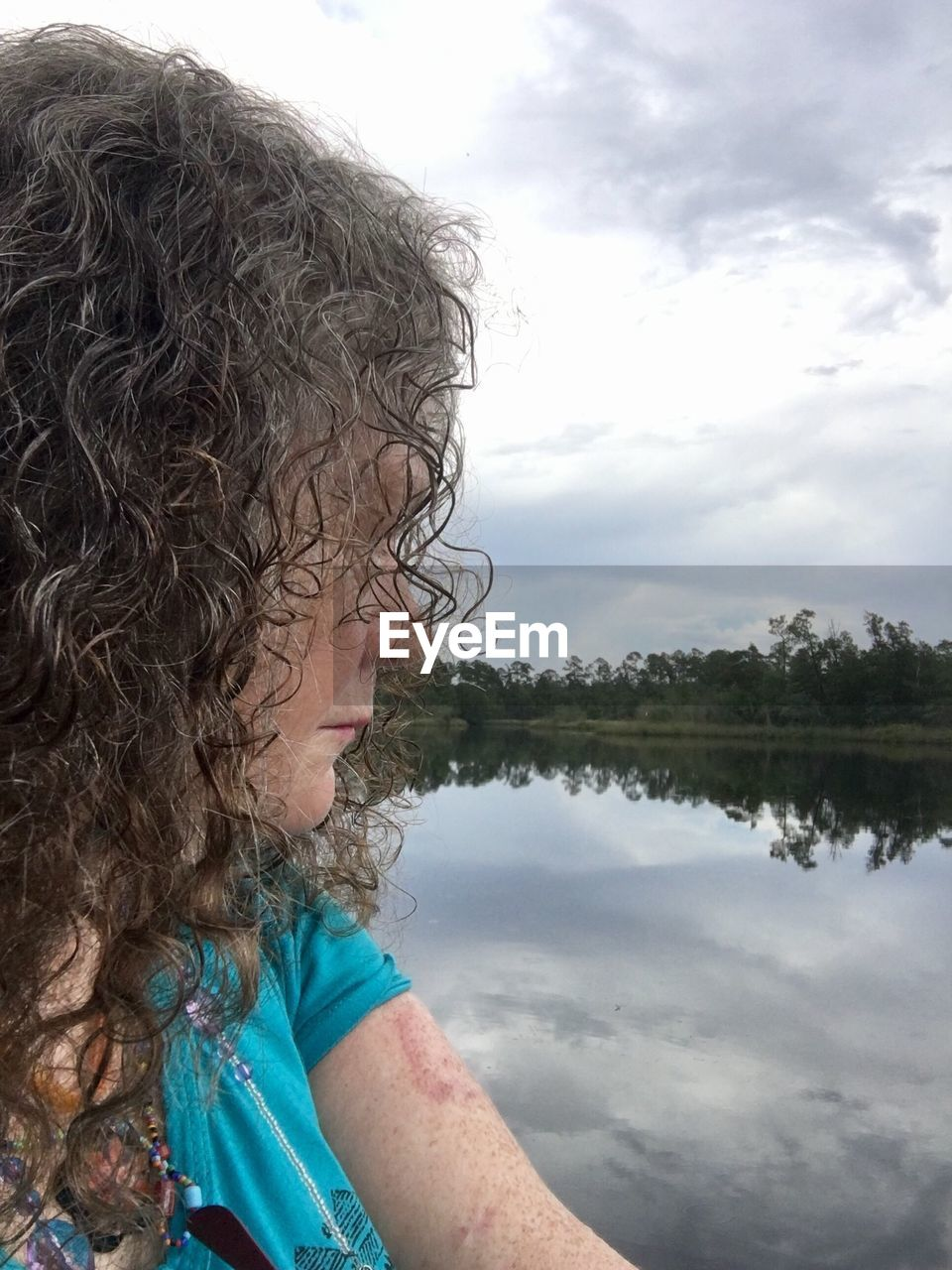 Side view of woman with curly hair looking at lake