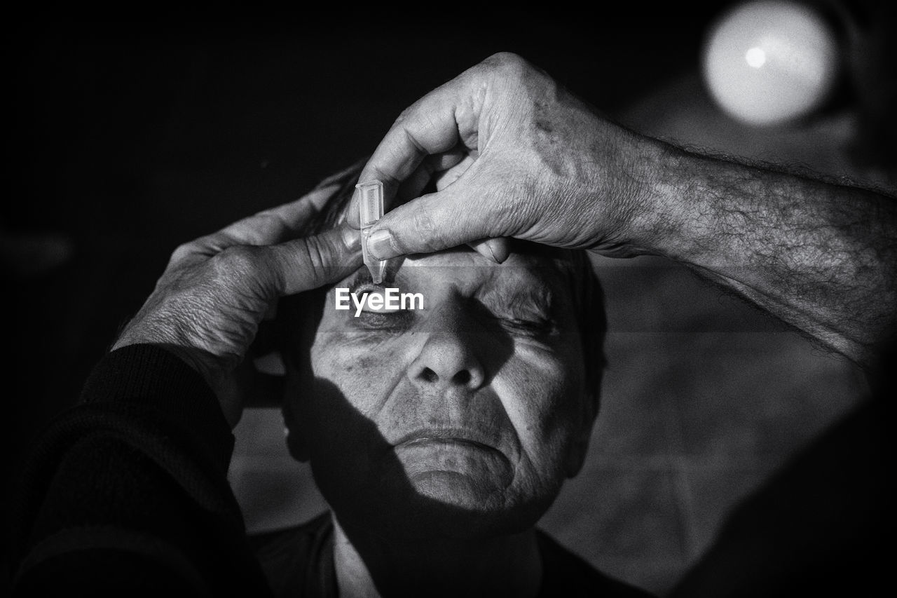 Cropped Hands Of Man Putting Eyedrops In Eye
