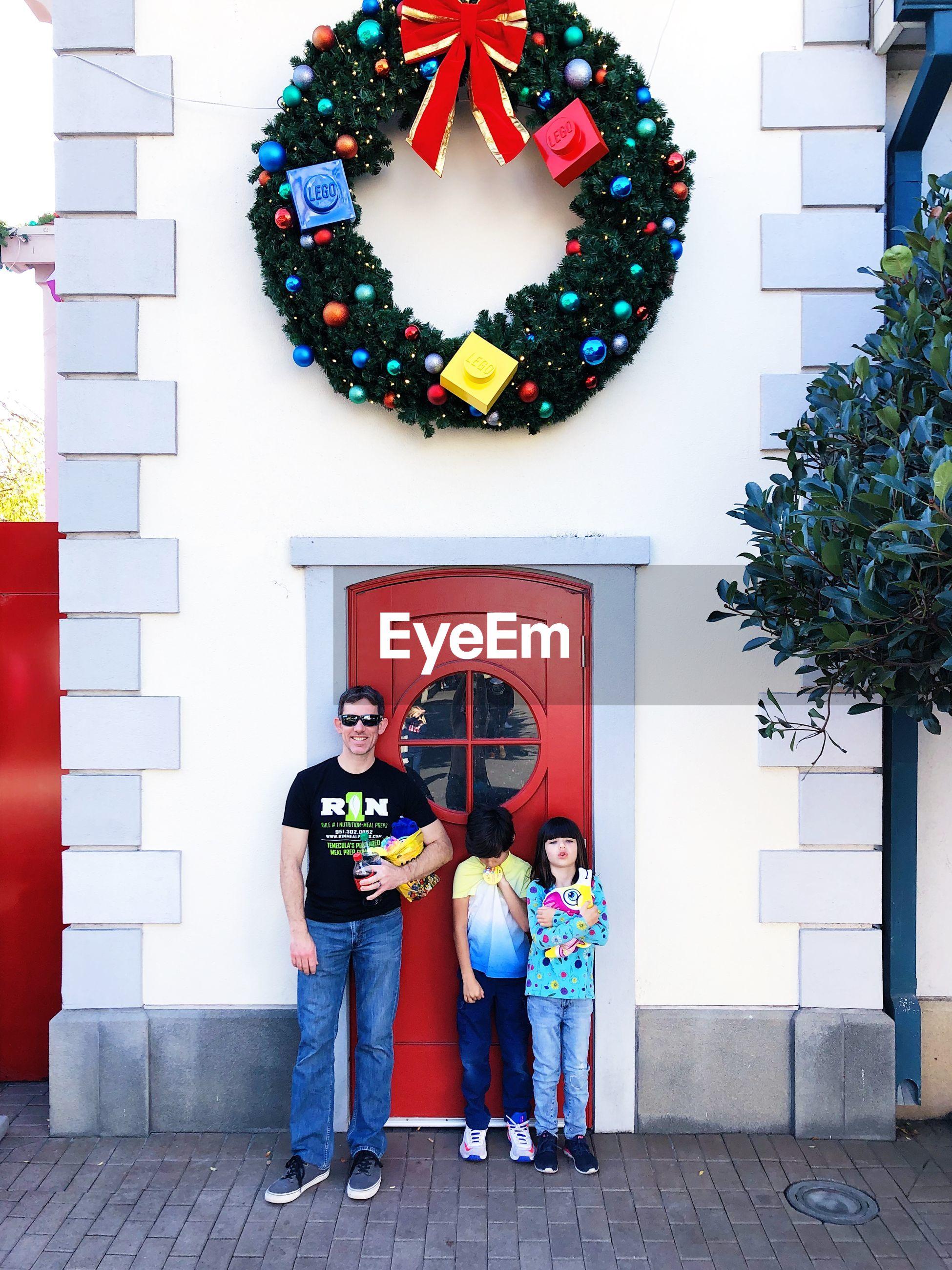 Portrait of family people standing against door
