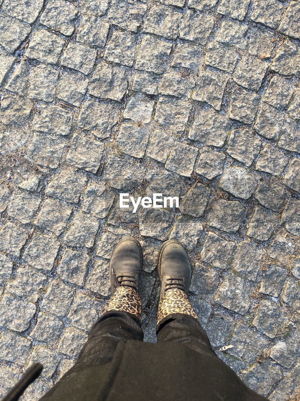 low section, human leg, shoe, body part, one person, human body part, personal perspective, real people, high angle view, standing, footpath, day, street, lifestyles, cobblestone, pattern, directly above, unrecognizable person, outdoors, human foot, human limb, jeans