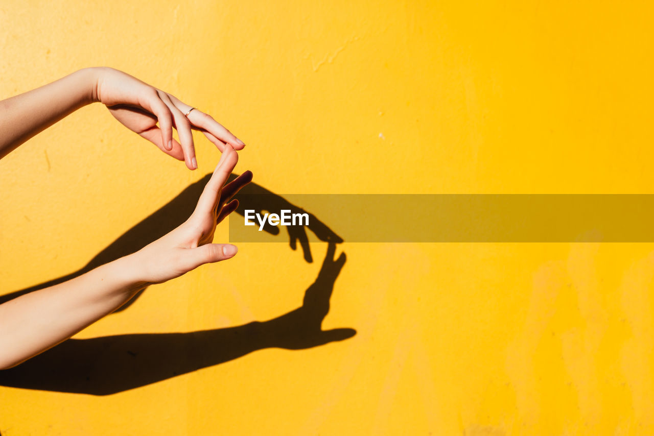Cropped Hands Of Woman Gesturing Against Yellow Wall