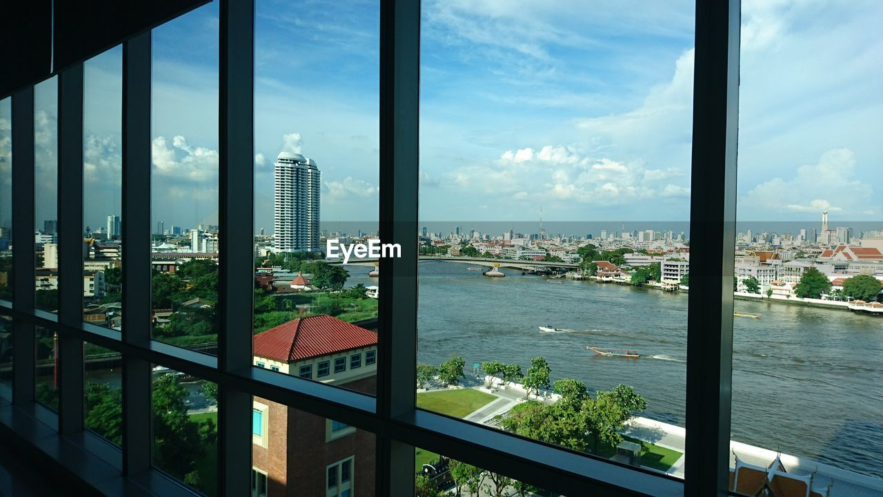 window, architecture, built structure, building exterior, city, transparent, cityscape, sky, no people, glass - material, nature, building, day, cloud - sky, outdoors, water, high angle view, plant, office building exterior, skyscraper, glass, window frame