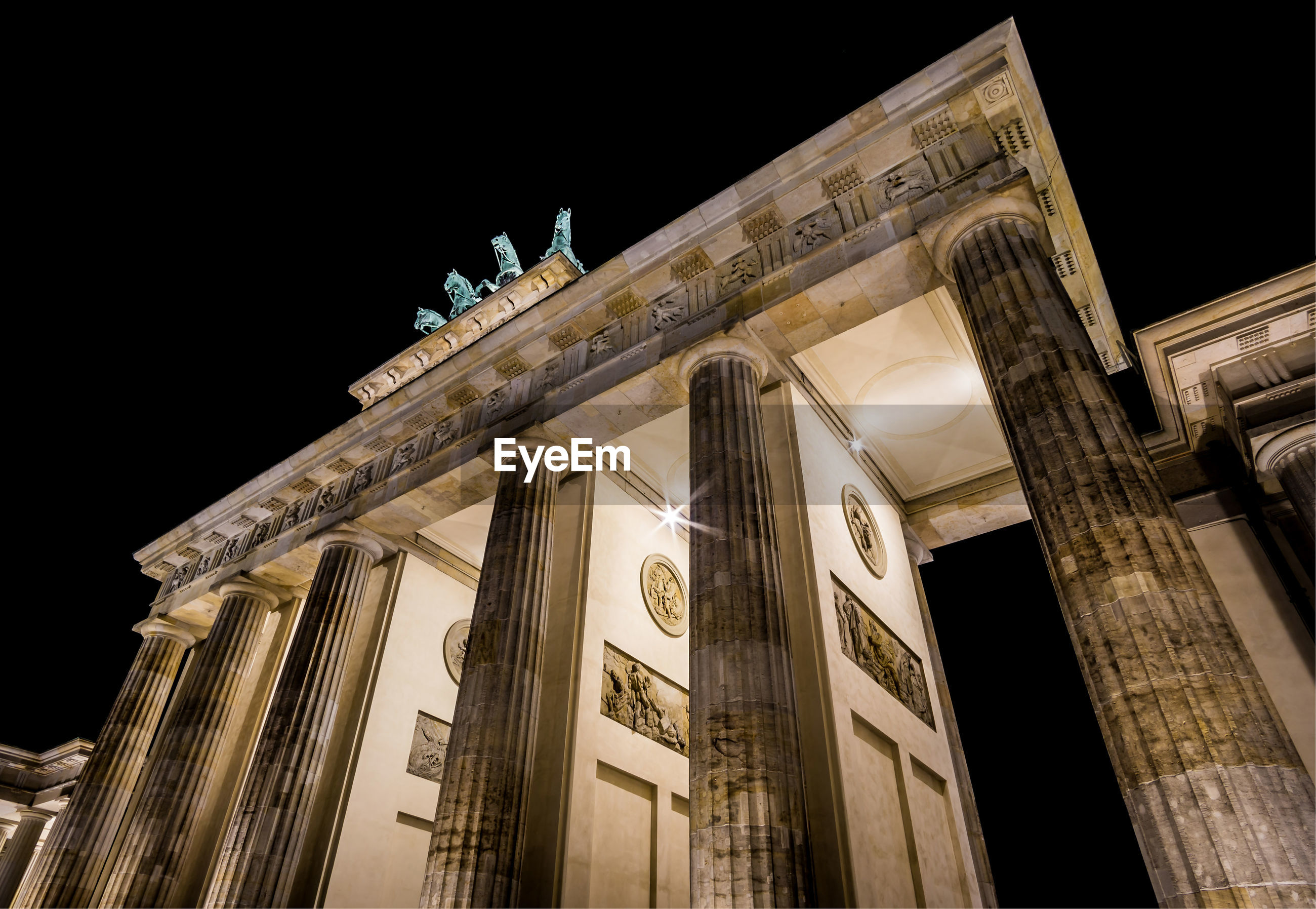 Low angle view of brandenburg gate against sky in city at night