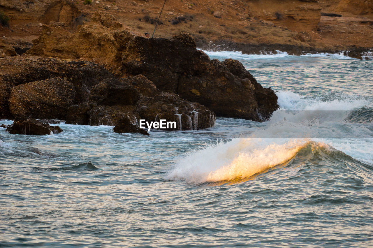 sea, water, motion, wave, sport, beauty in nature, splashing, rock, power, power in nature, rock - object, aquatic sport, surfing, solid, nature, waterfront, scenics - nature, day, outdoors, hitting, breaking