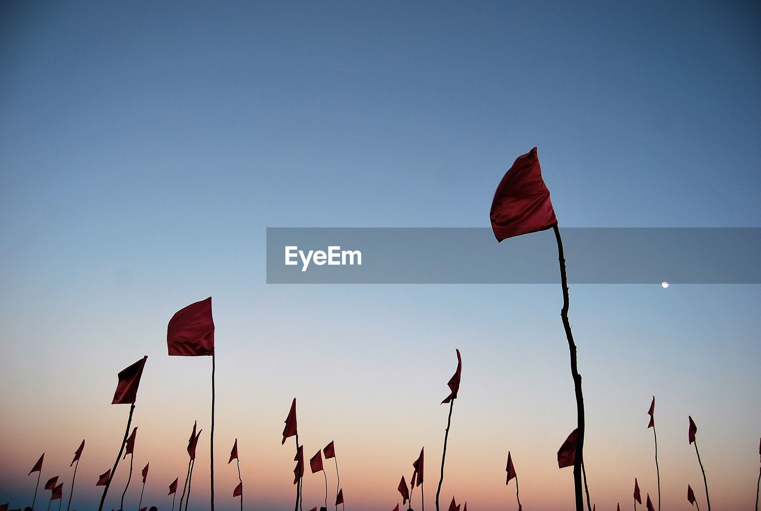 Low angle view of red flags waving against clear sky at dusk
