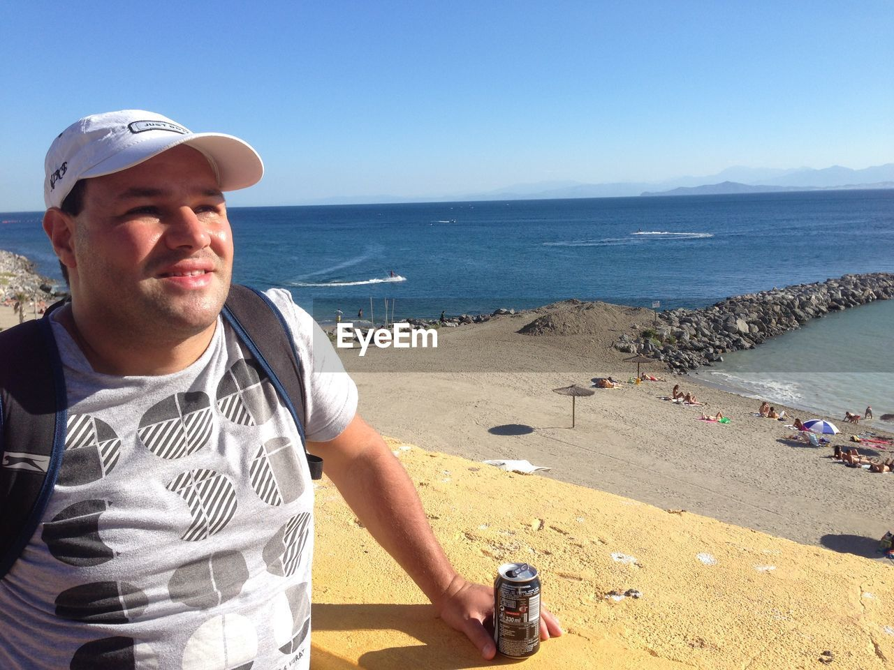 Mid Adult Man With Drink Can Against Beach