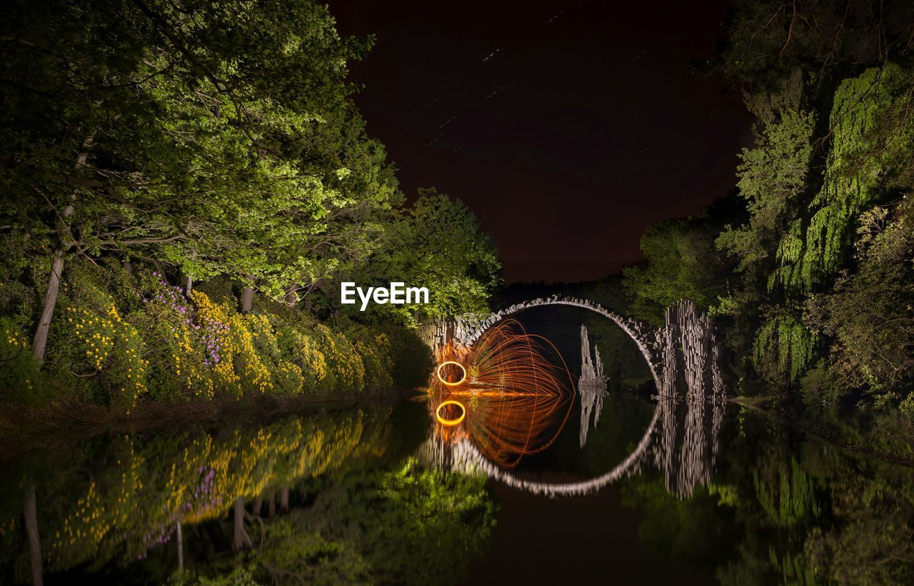 Illuminated wire wool amidst trees with reflection in water