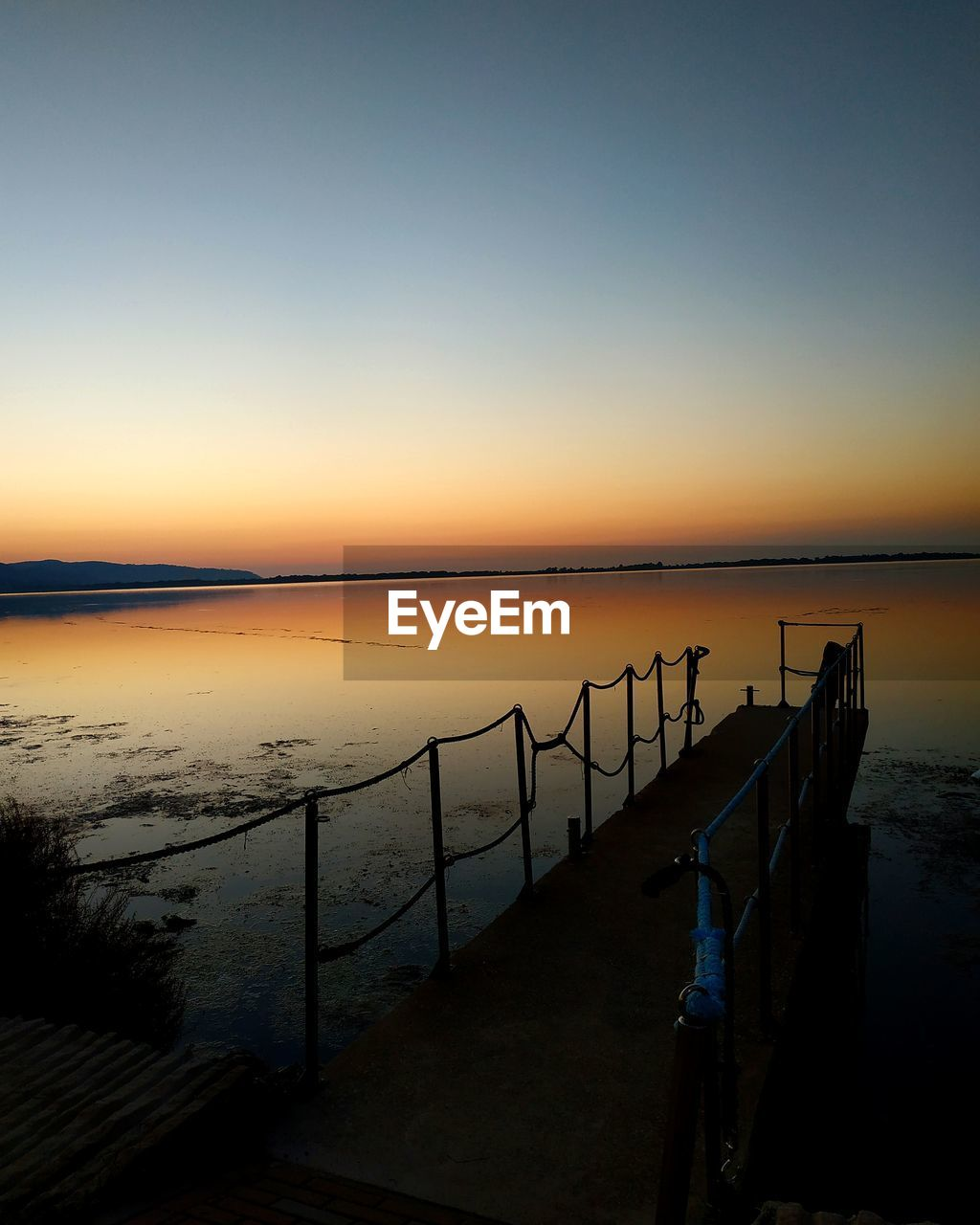sky, sunset, water, scenics - nature, tranquility, tranquil scene, railing, beauty in nature, sea, clear sky, nature, copy space, idyllic, beach, non-urban scene, no people, orange color, horizon, outdoors, wooden post