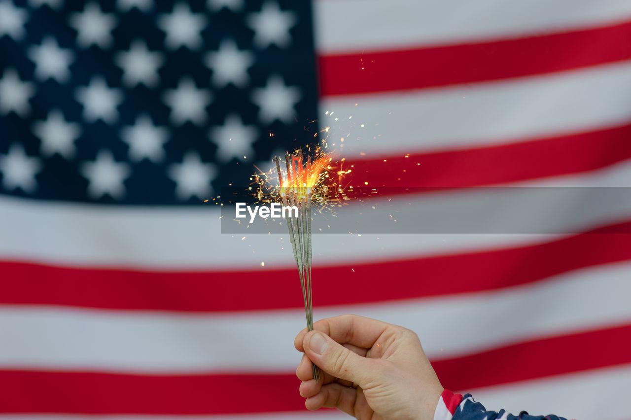 red, holding, celebration, human hand, hand, sparkler, motion, one person, patriotism, human body part, firework, burning, event, flag, sparks, real people, firework - man made object, firework display, finger