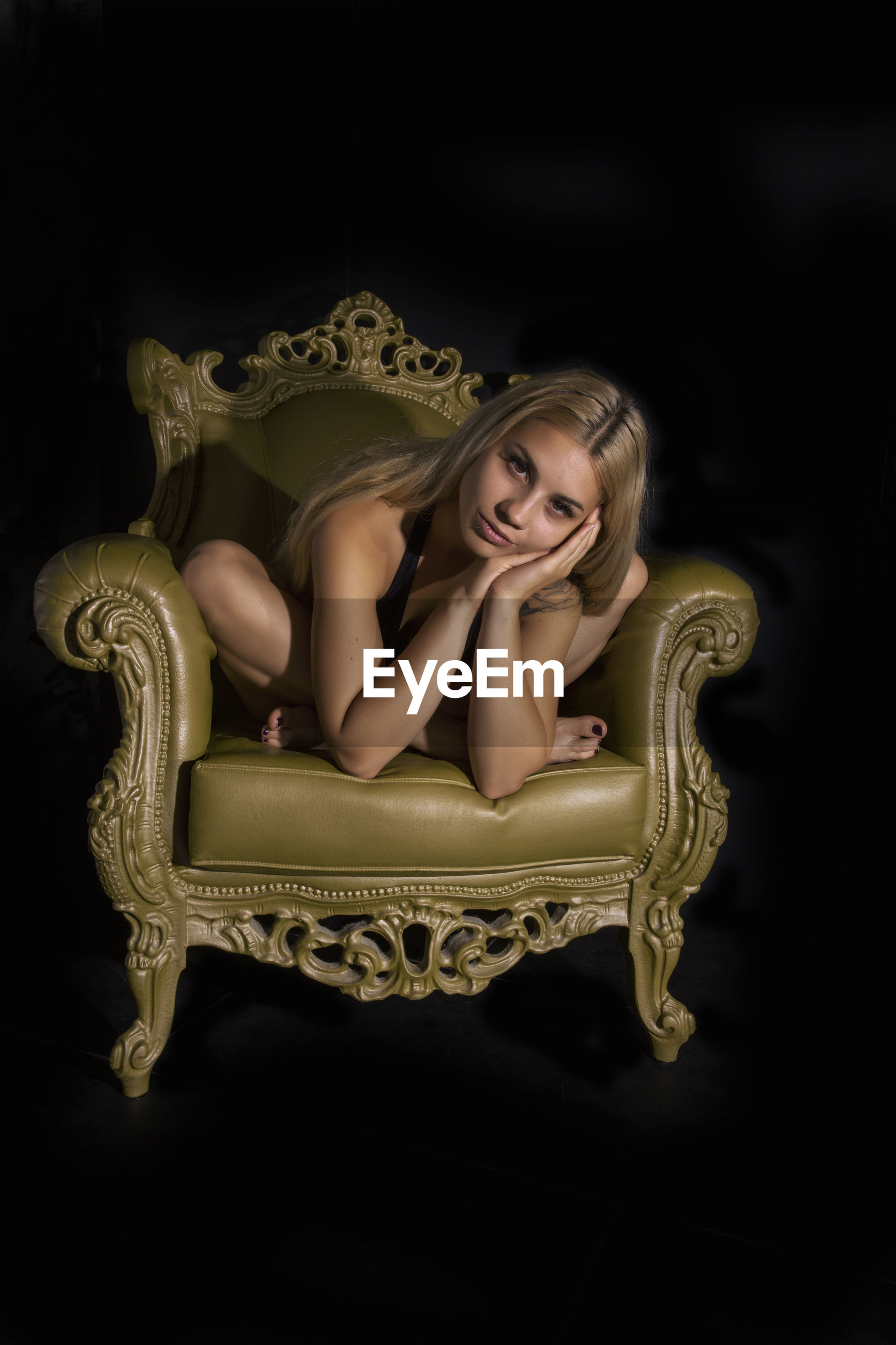 Portrait of woman sitting on chair in darkroom
