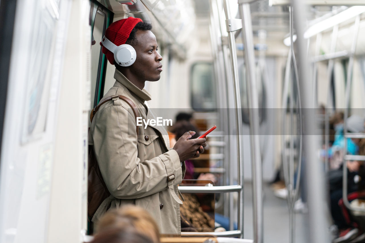 Side view of man using mobile phone in train