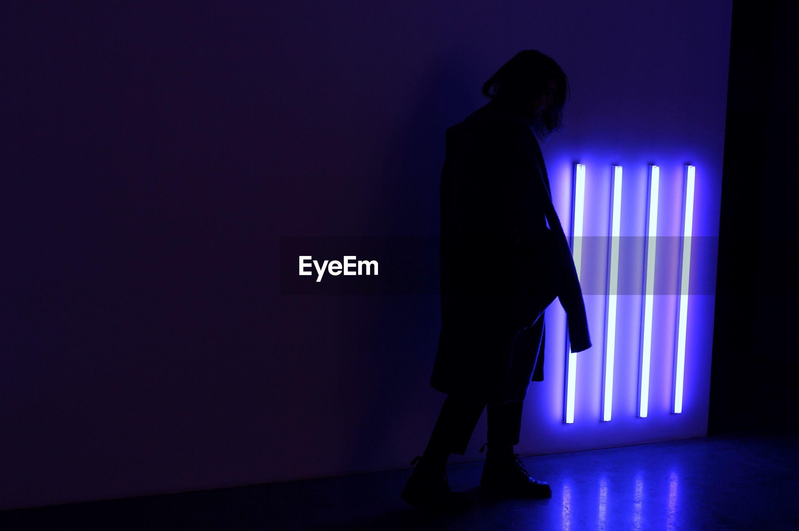 SILHOUETTE MAN STANDING BY ILLUMINATED LIGHT