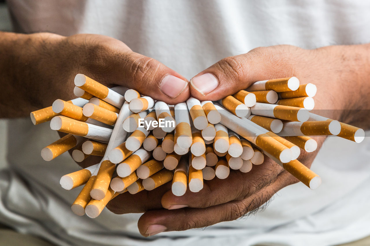 Midsection of man holding cigarettes