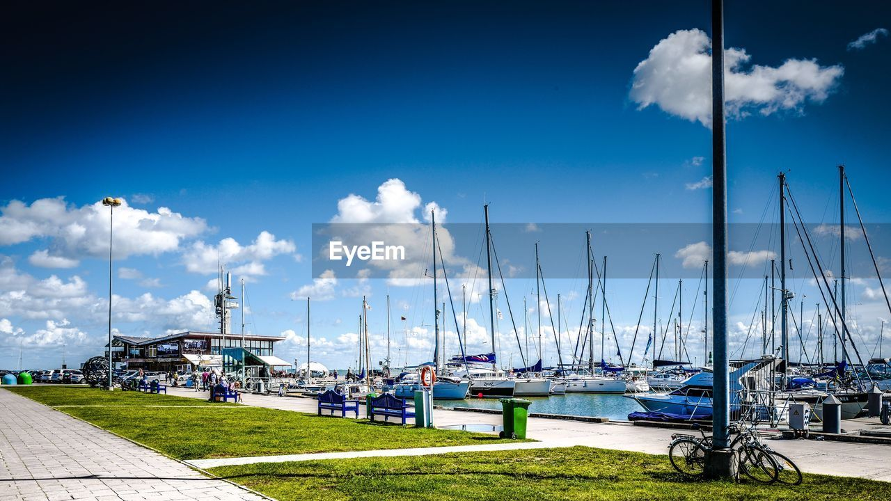 sky, cloud - sky, transportation, mode of transportation, nautical vessel, sailboat, nature, harbor, water, mast, day, moored, no people, pole, grass, blue, architecture, outdoors, sunlight, marina