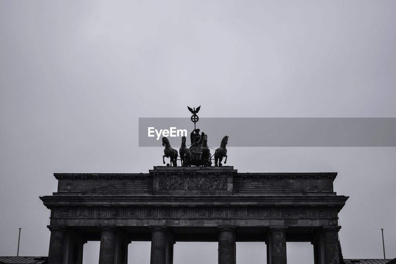 Low angle view of statues on brandenburg gate against sky