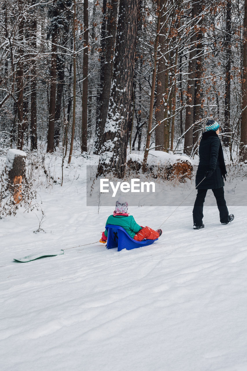 REAR VIEW OF BOYS ON SNOW COVERED LAND