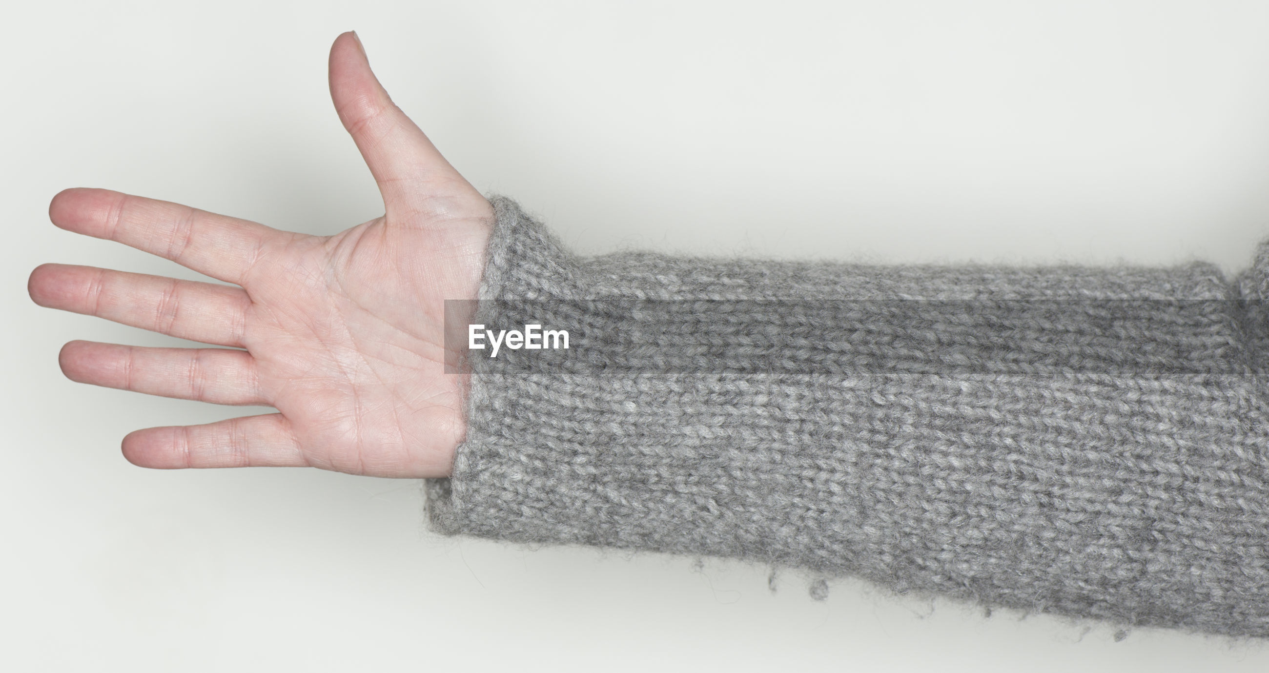 Cropped hand of woman in gray sweater gesturing against white background