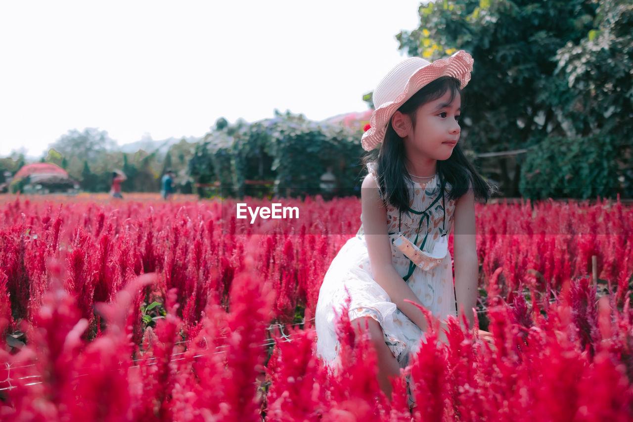Woman standing by flower field