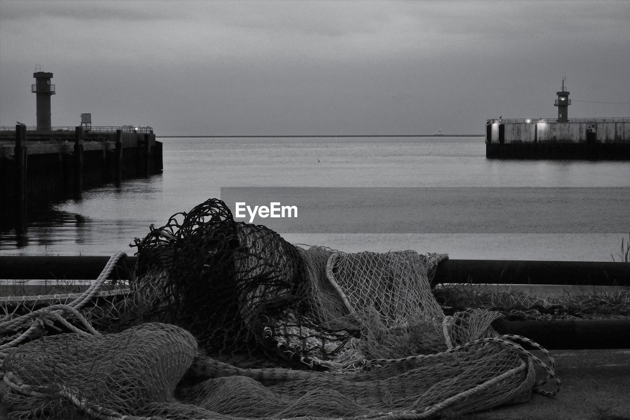 Black and white of pier against evening sky. gate to the open sea