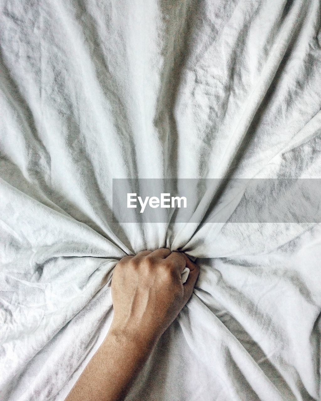 Close-Up Of Hand Gripping Crumpled Bedsheet