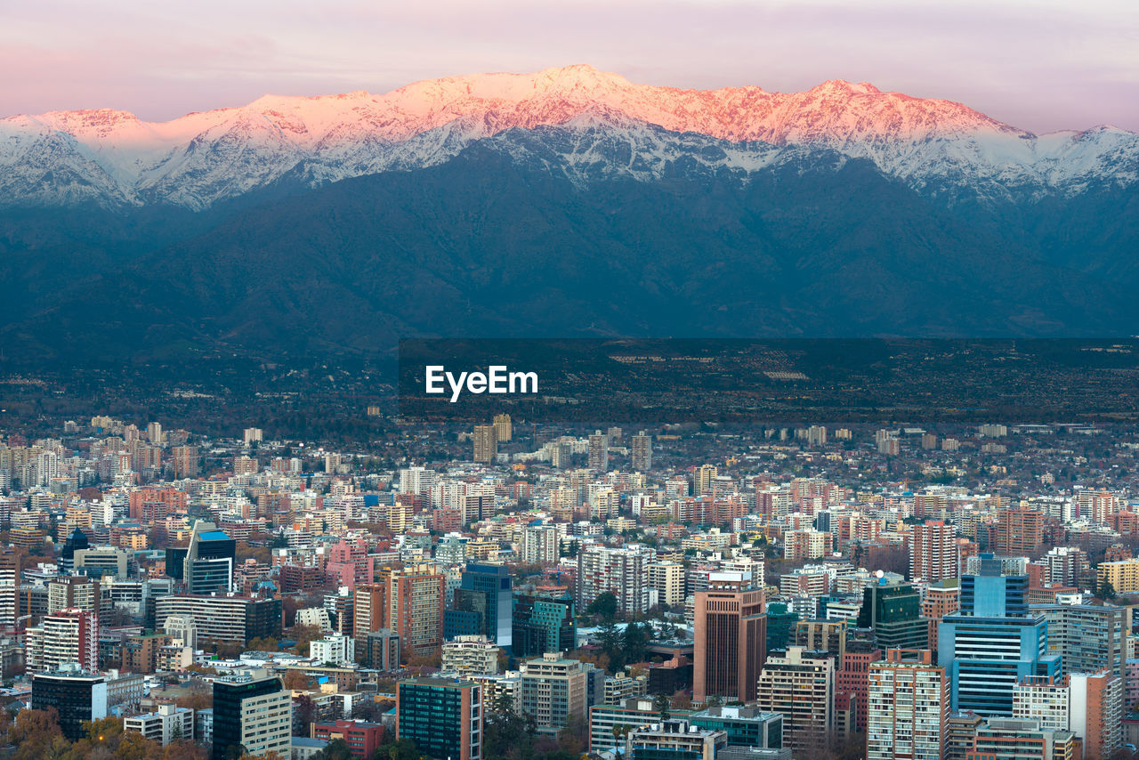 Aerial View Of Buildings In City Against Mountains During Winter