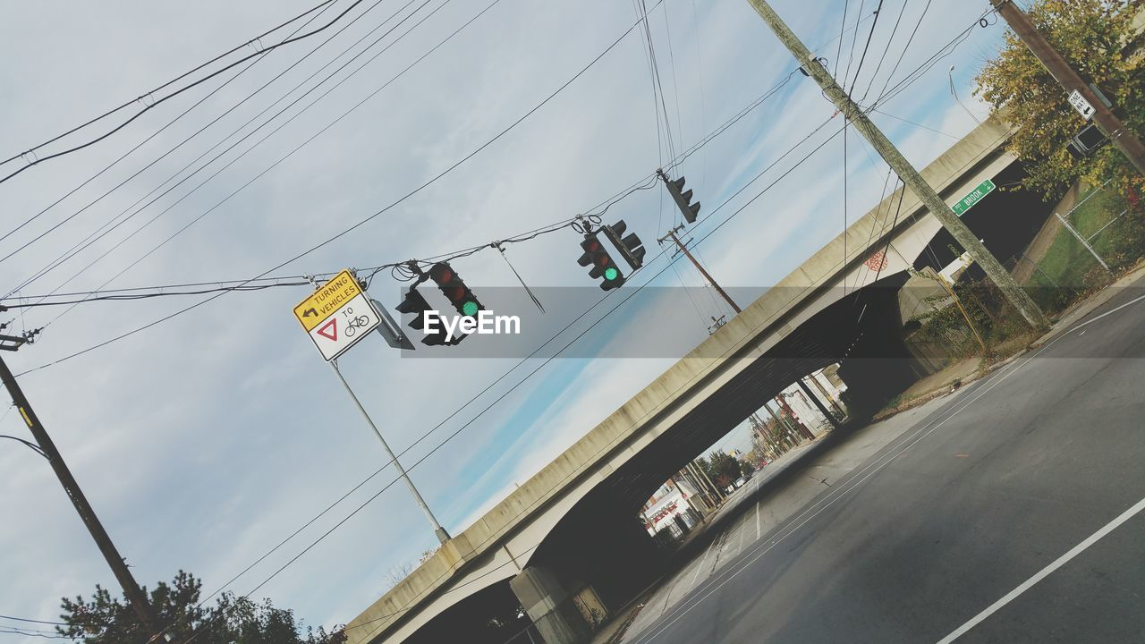 Tilt Shot Of Signals Hanging Over Highway Against Sky