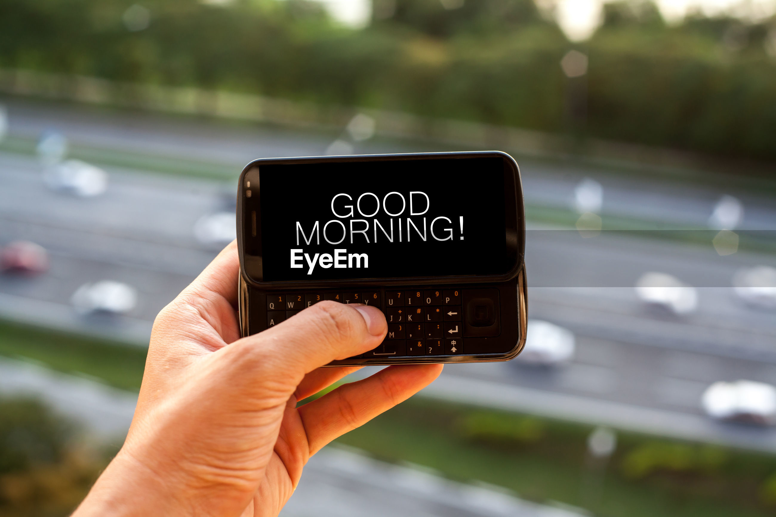 Cropped hand typing good morning text in mobile phone