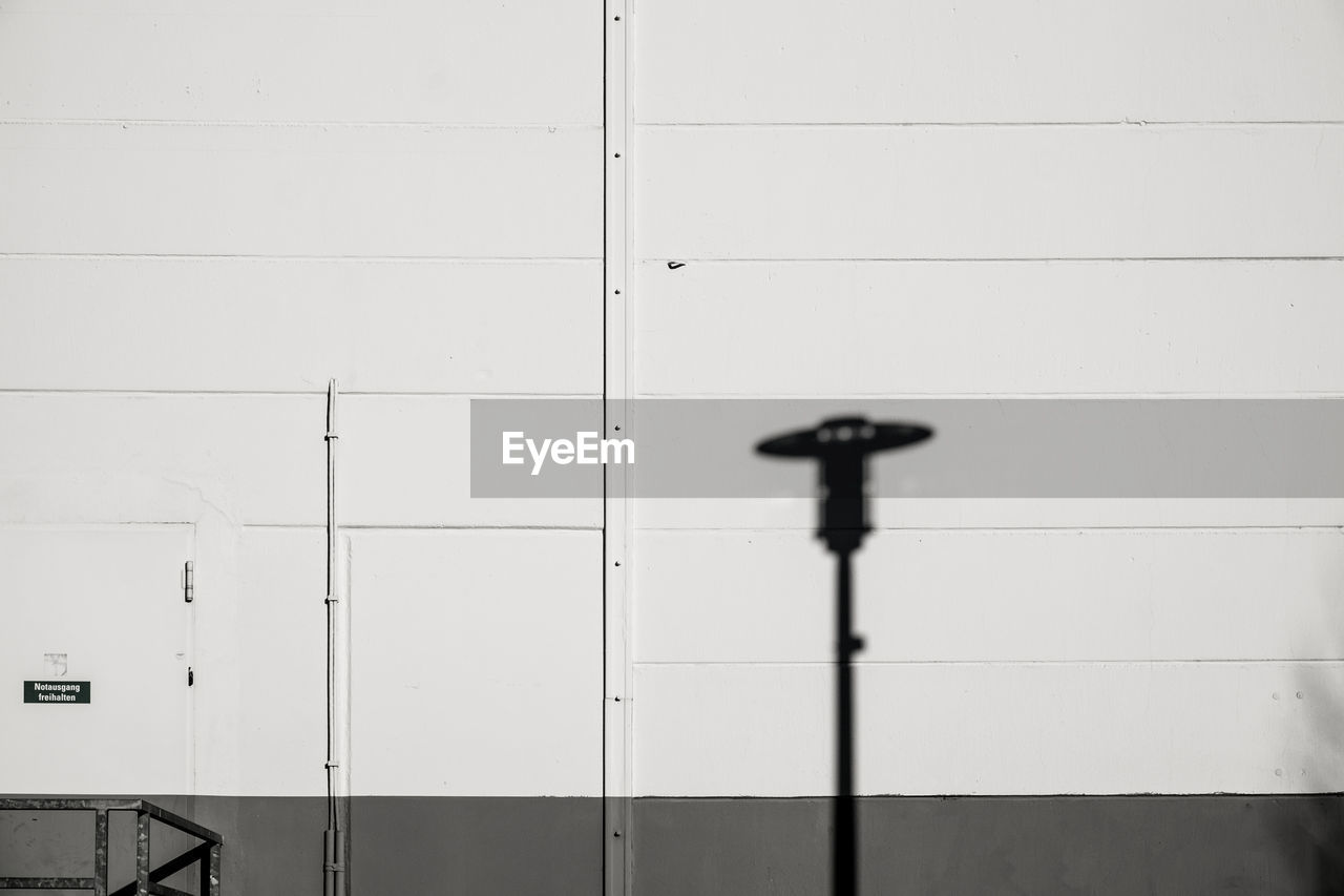 Shadow of lamp post on wall