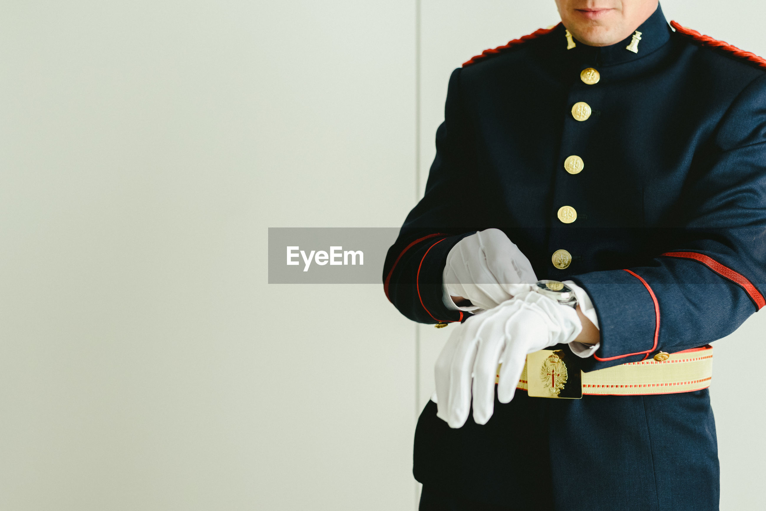 Midsection of army soldier wearing gloves standing at home