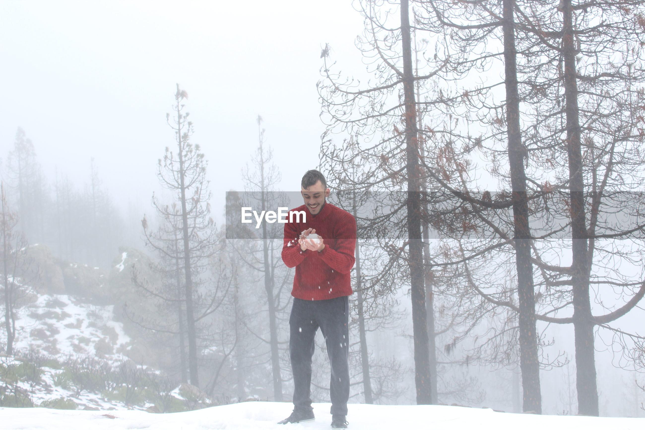 Full length of man holding snow against trees