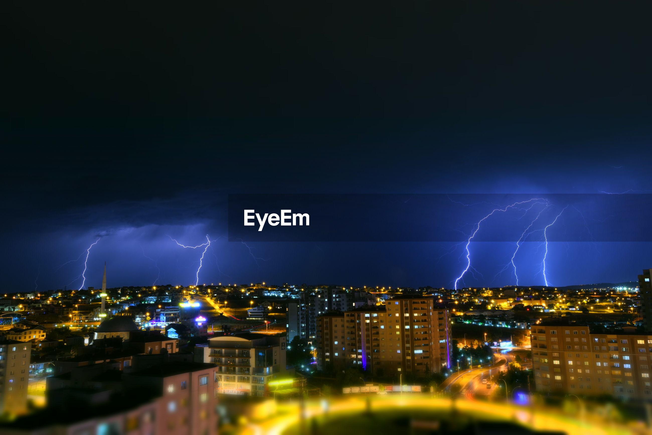 Lightning over illuminated cityscape at night